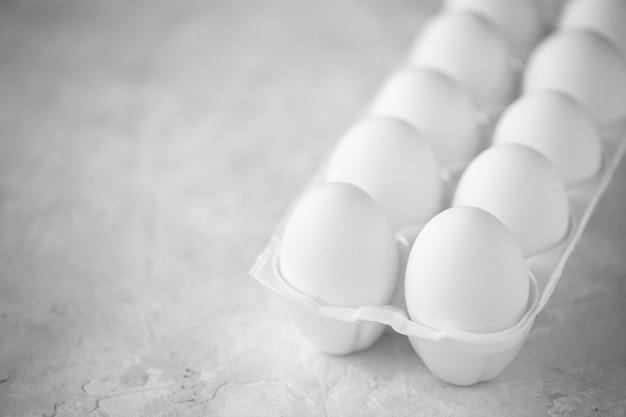Группа белых яиц в пакете, серый фон, место для текста. выборочный фокус