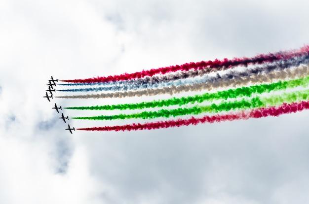 青い空を背景にカラフルな煙の痕跡と白い戦闘機の飛行機のグループ。