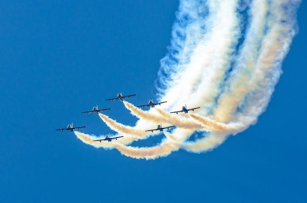 青い空に白い煙の痕跡がある白い戦闘機のグループ。