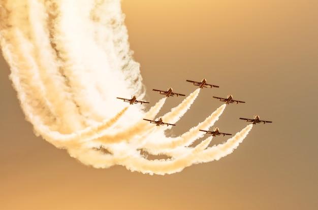 青い空を背景に白い煙の痕跡を持つ白い戦闘機のグループ。