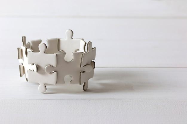 나무 테이블에 흰색 직소 퍼즐의 그룹입니다. 비즈니스 팀워크와 협력 개념.