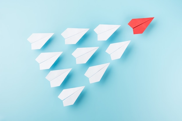 Группа белой бумаги плоскости и один красный самолет на синем