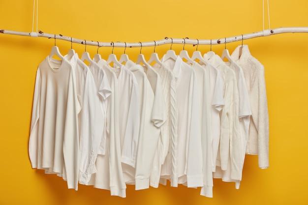 衣服ラックまたはレールにぶら下がっている白い私服のグループ。ミニマルなコンセプト。黄色の背景で隔離の女性のためのアパレル。