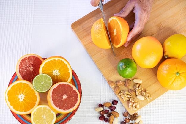 全体と半分の柑橘系の果物のグループ、オレンジを切る女性の手で木製のまな板。グレープフルーツ、ライム、ドライフルーツ