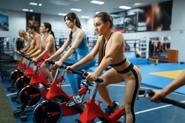 체육관에서 고정식 자전거 운동을하는 여성 그룹