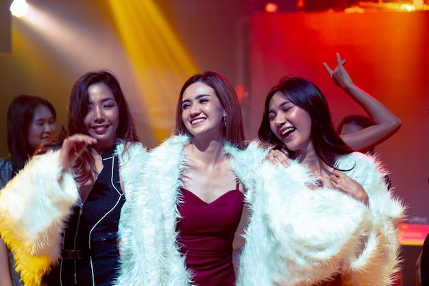 Группа друзей женщин весело на вечеринке в танцевальном клубе