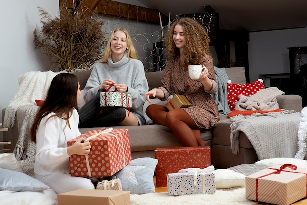 집에서 재미 포장 선물을 가진 여성 그룹, 크리스마스 선물을 포장하는 친구의 훌륭한 팀워크