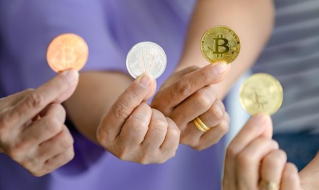 さまざまな色のビットコインを持ってカメラに見せてくれる女性のグループ。暗号通貨とお金のビジネスコンセプト。