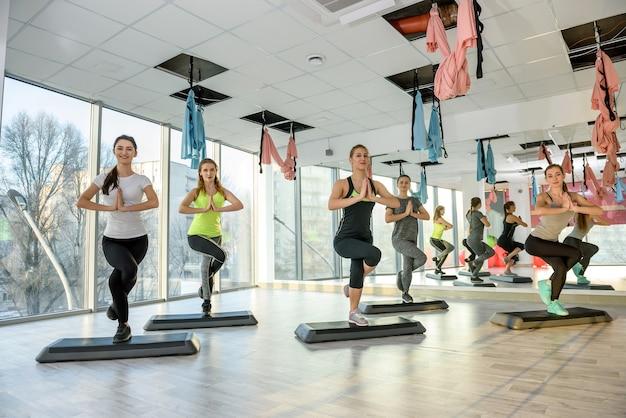 Группа женщин в тренажерном зале, делая упражнения на балансировку