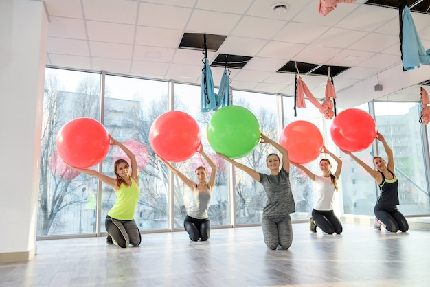 Группа женщин в тренажерном зале, делая упражнения на мяч