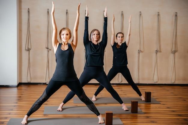 Группа женщин, практикующих растяжку йоги с использованием деревянных блоков, упражнения на гибкость позвоночника и плеч