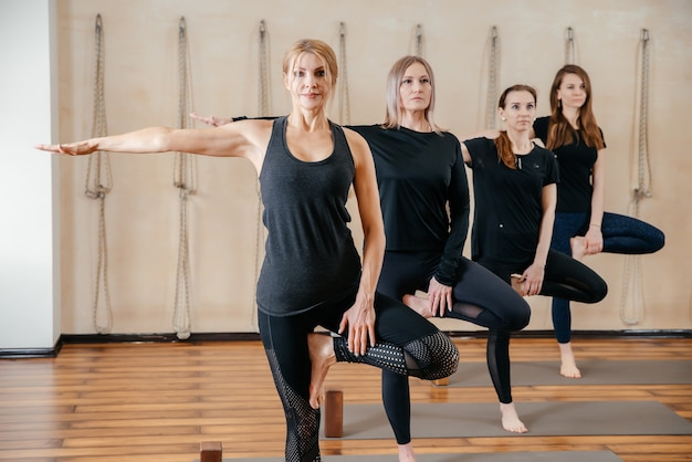 Группа женщин, практикующих растяжку йоги с использованием деревянных блоков, упражнения для позвоночника и плеч