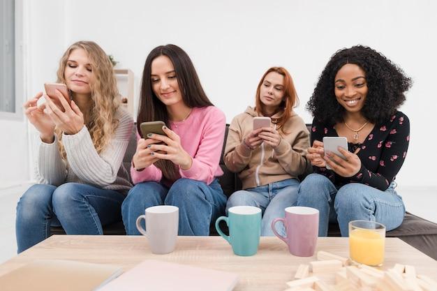 그들의 전화에 함께 시간을 보내는 여성 그룹