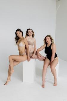 다른 신체와 인종을 가진 여성 그룹이 여성의 힘과 힘을 보여주기 위해 함께 포즈를 취하여 여성의 신체 개념 고품질 사진