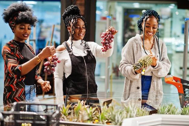 식료품가 게 슈퍼마켓에서 이국적인 과일을 구입하는 쇼핑 카트를 가진 여자의 그룹