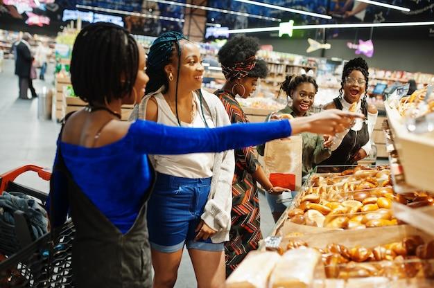 Группа женщин с тележками возле хлебобулочных изделий в супермаркете