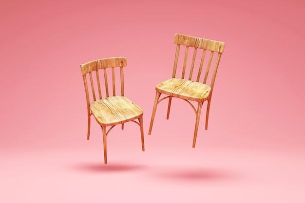 ピンクのスタジオの背景に木製の椅子の浮揚のグループ