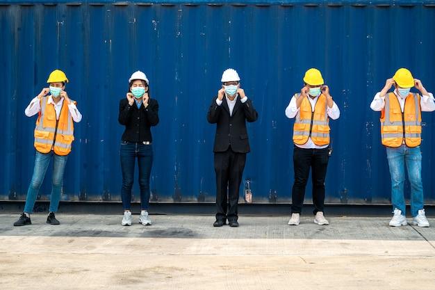 労働者のグループは、社会的距離のある建設現場で保護フェイスマスクと安全ヘルメットを着用しています