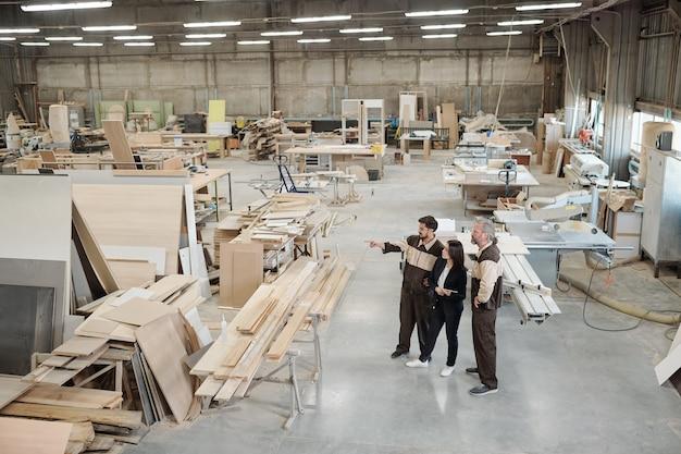 Группа рабочих современной фабрики обсуждает материалы для производства мебели, в то время как менеджер по продажам указывает на них на встрече