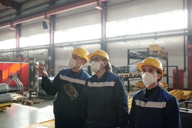 작업장에서 새로운 산업 기계를 보고 토론하는 보호 작업복과 인공 호흡기를 착용한 작업자 또는 엔지니어 그룹