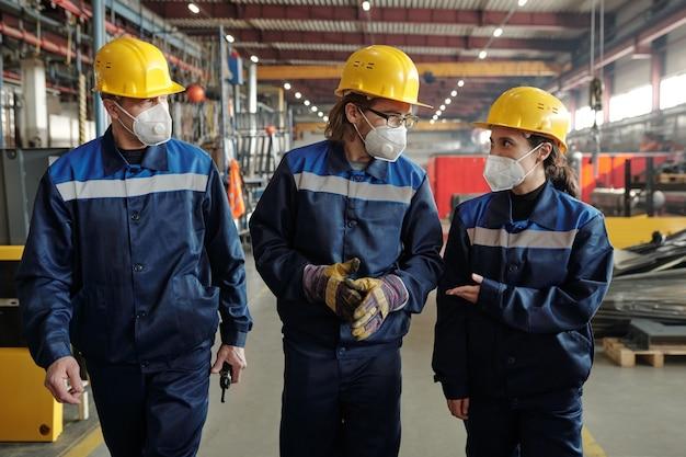 장비 및 컨설팅과 함께 작업장을 따라 이동하는 보호 작업복 및 인공 호흡기를 착용한 작업자 또는 엔지니어 그룹
