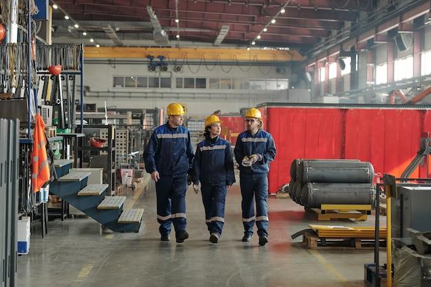 현대 공장의 노동자 또는 엔지니어 그룹이 산업 장비를 가지고 큰 작업장을 따라 이동하고 대화를 나누고 있습니다.