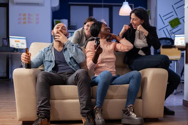コントローラーのジョイスティックを使用しながらオフィスでvrメガネでゲームをしている労働者のグループ。多様なチームがエンターテインメントを楽しむためのお祝いパーティーで友情の絆を深める