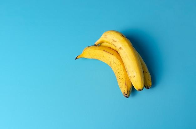 青い背景の空白のスペースに分離された黄色いバナナのグループ
