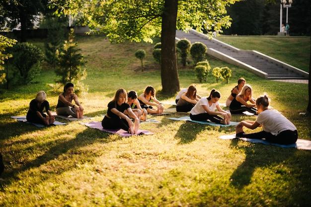 한 무리의 요기니 여성들이 강사의 지도 하에 여름 화창한 아침에 도시 공원에서 근육을 스트레칭하고 있습니다. 사람들의 그룹이 푸른 잔디에 요가 포즈에 앉아 있다