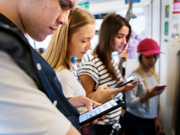 Группа молодых взрослых друзей, использующих смартфоны в метро