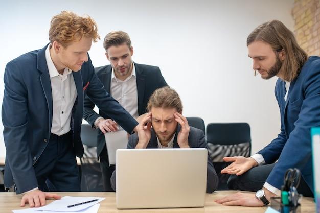 Группа молодых взрослых мужчин в костюмах собралась вместе возле ноутбука, работающего в офисе