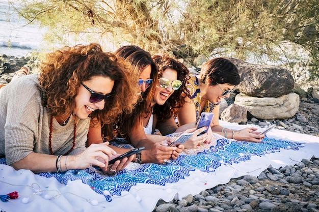 Группа молодых взрослых женщин вместе пользуются современными телефонами, веселятся и много смеются