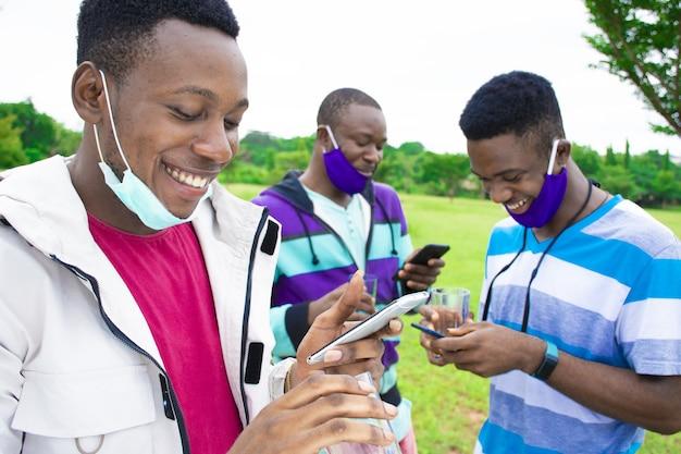 公園で社会的な距離を置いている間電話を使用してフェイスマスクを持つ若いアフリカの友人のグループ