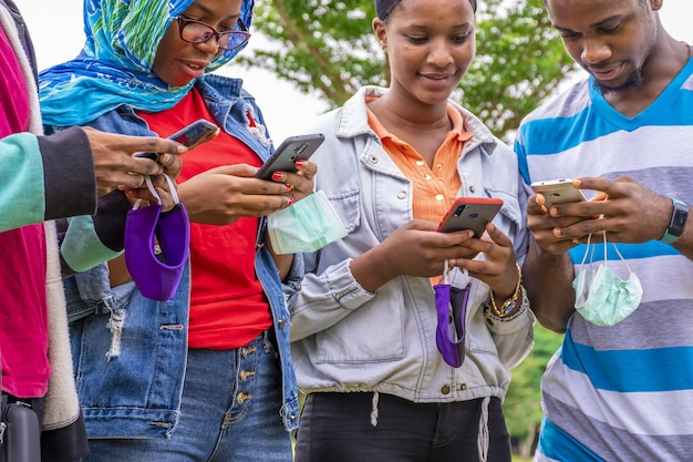 公園で携帯電話を使用してフェイスマスクを持つ若いアフリカの友人のグループ