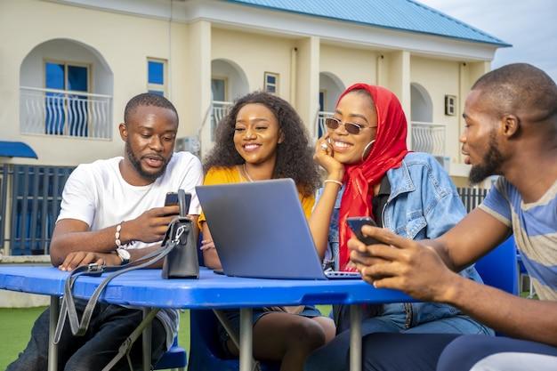 Группа молодых африканцев тусуется в летнем кафе
