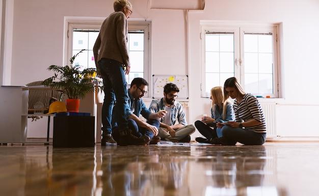 젊고 헌신적 인 동료 그룹이 팀 빌딩 운동에 모여 창문 근처의 큰 방 바닥에 앉아 있습니다.