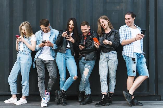 Группа молодых и стильных людей, использующих смартфоны вместо реального общения