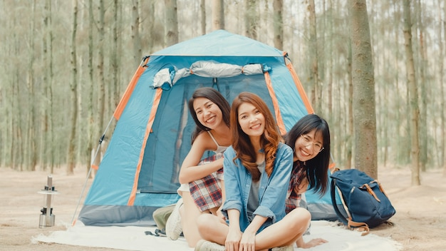 近くでキャンプする若いアジアのキャンピングカーの友人のグループは、森での瞬間を楽しんでください