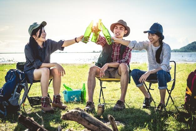 Группа молодых азиатских друзей наслаждаются пикником и вечеринкой на озере с кемпинговым рюкзаком