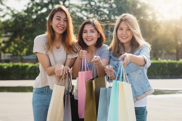 ショッピングカートで屋外市場で買い物をする若いアジア人女性のグループ