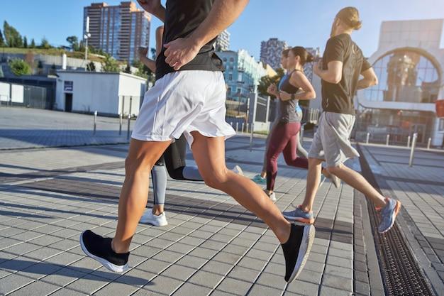 舗装された歩行者エリアに沿って走っている若いアスリートのグループ