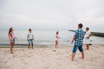Group of young attractive friends playing frisbee on the beach, by the sea
