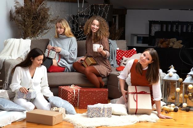 젊은 매력적인 여성 그룹은 아늑한 집 분위기에서 크리스마스 선물 포장 재미를 가지고
