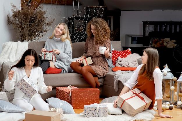 젊은 매력적인 여성 그룹은 아늑한 가정 분위기에서 크리스마스 선물 포장 재미를 가지고