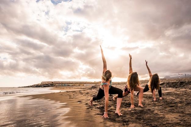 海岸のビーチでフィットネスエクササイズをしている若い美しい白人女性のグループ