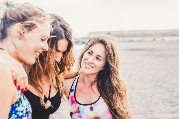 若い美しい女性の友人のグループは、屋外のビーチで一緒に抱き合って友情を楽しんでいます-健康な人々のための観光とスポーツ活動-白人の女の子