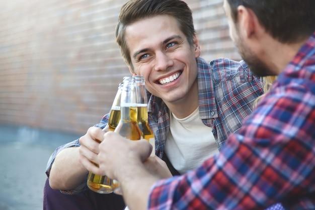 通りでビールを楽しんでいる若い親友のグループ。