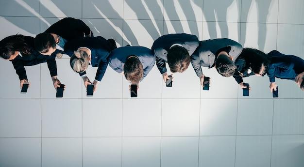 スマートフォンの画面を見ている若いビジネスマンのグループ。コピースペース付きの写真。