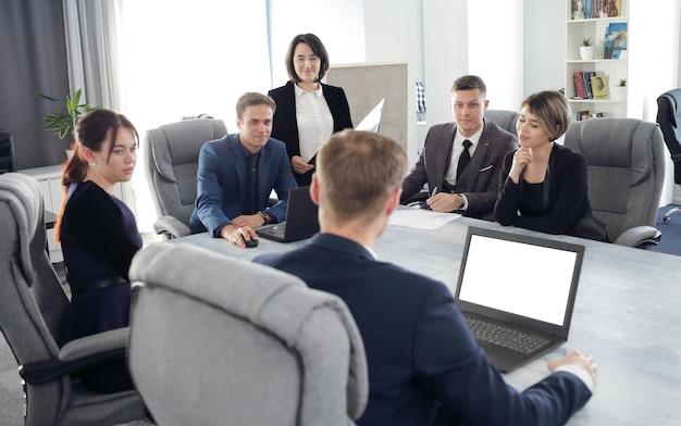 Группа молодых деловых людей, встречающихся в офисе, вместе обсуждают важную идею.
