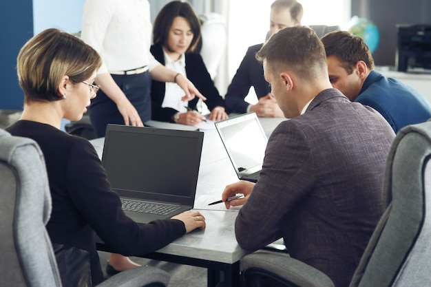 Группа молодых деловых людей, встречающихся в офисе, весело вместе обсуждая идею.